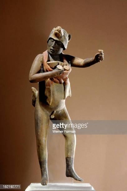 Nude male figure of a dancer holding a bunch of flowers in each hand He wears a pouch with more flowers around his neck and a coyote head as a...