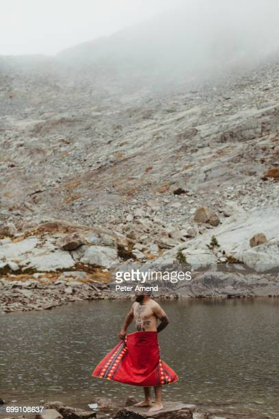 'Nude male hiker wrapping himself in towel at lake, Mineral King, Sequoia National Park, California, USA'