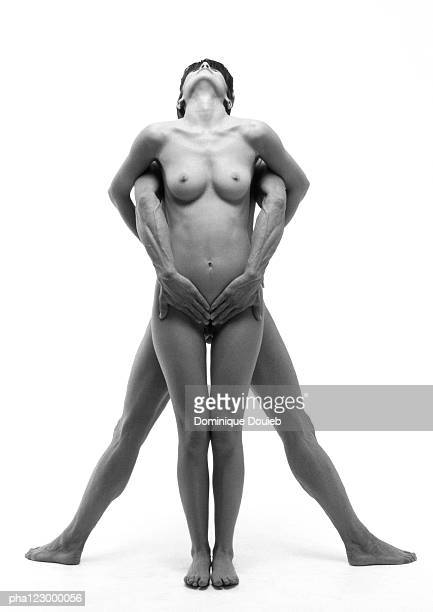 Nude man and nude woman, back to back, embracing and looking up, B&W