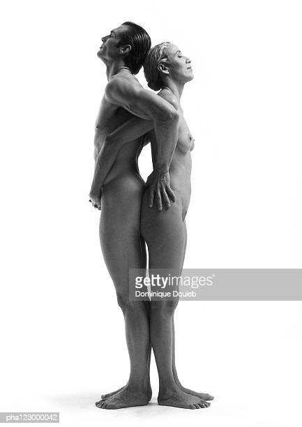 Nude man and nude woman, back to back, hands on each other's hips, B&W