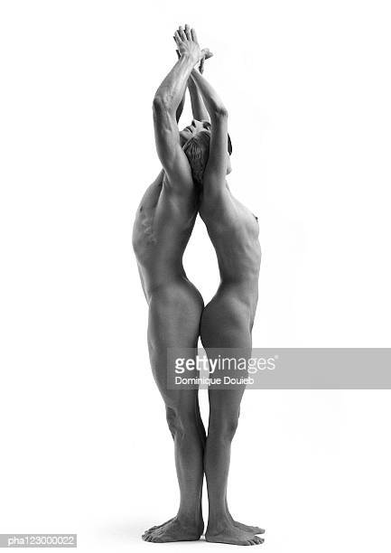 Nude man and nude woman, back-to-back, arms raised together and pointing upward, B&W