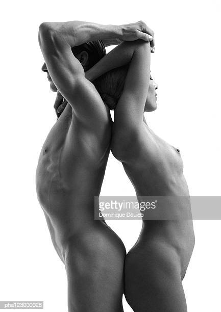 Nude man and nude woman, back-to-back, holding arms over head, B&W