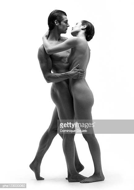 Nude man and nude woman embracing face to face, B&W
