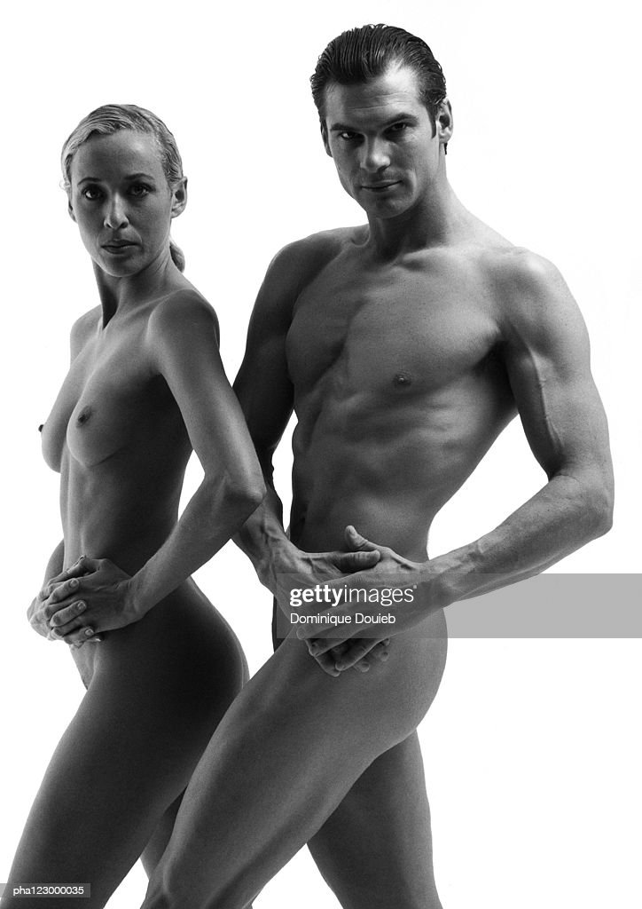 Nude man and nude woman facing forward, hands on hips, B&W : Stockfoto