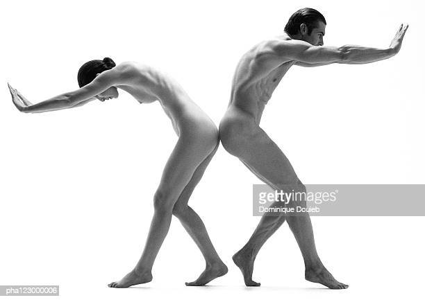 Nude man and nude woman facing opposite directions, leaning forward, pushing arms out, B&W