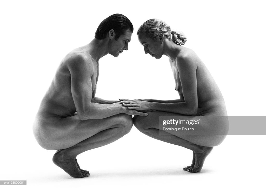 Nude man and nude woman kneeling face to face, holding hands, B&W : Stockfoto