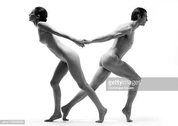 nude man and nude woman leaning away from each other, holding hands from behind, b&w - pareja desnuda fotografías e imágenes de stock