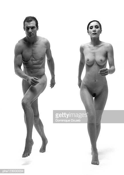 Nude man and nude woman running side by side, frontal view, B&W