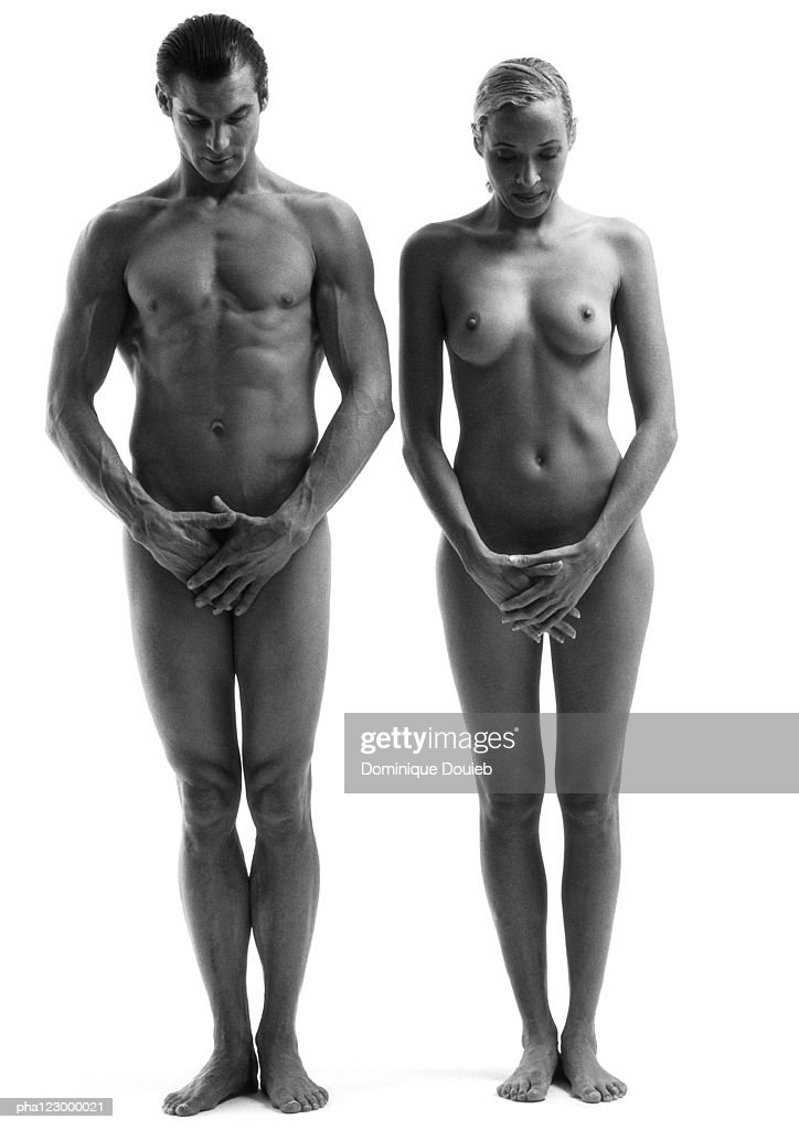 Nude man and nude woman standing side by side, heads down, hands crossed on hips, B&W : Stock Photo