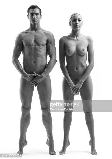 Nude man and nude woman standing side by side with feet extended, hands over hips, B&W