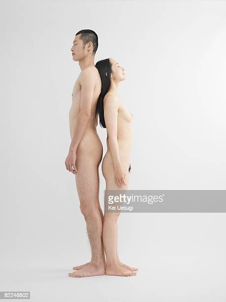 Nude man and woman standing, back to back