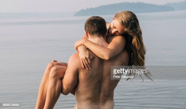 nude man carrying nude woman into water - women skinny dipping stock pictures, royalty-free photos & images