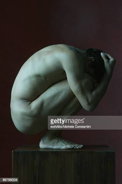 Nude man crouching in fetal position, head in hands, side view