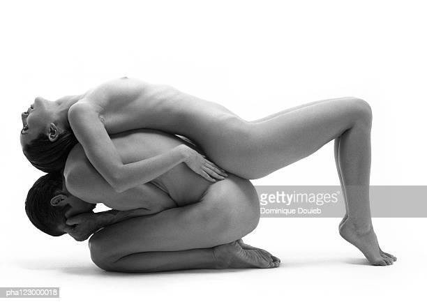Nude man curled in ball with nude woman laying on back, B&W