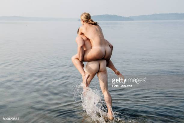Nude man giving nude woman piggyback into water