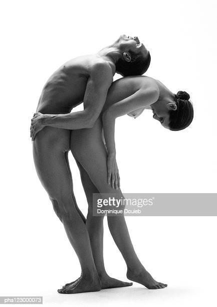 Nude man leaning back to back over nude crouching woman, B&W
