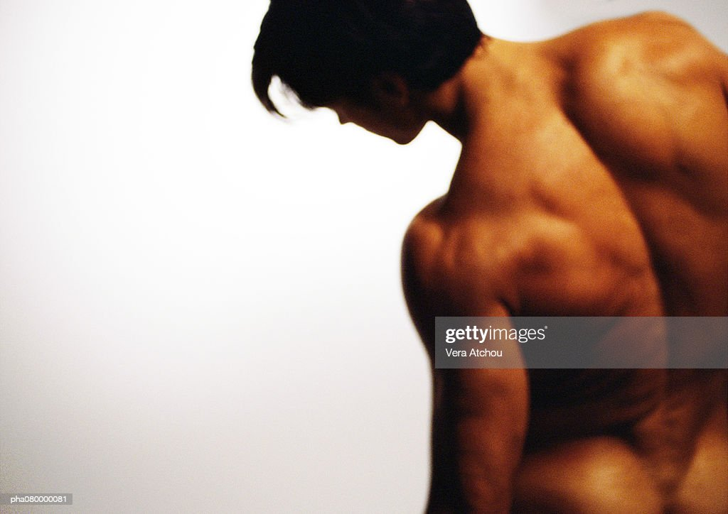 Nude man leaning to side, rear view, off center : Stockfoto