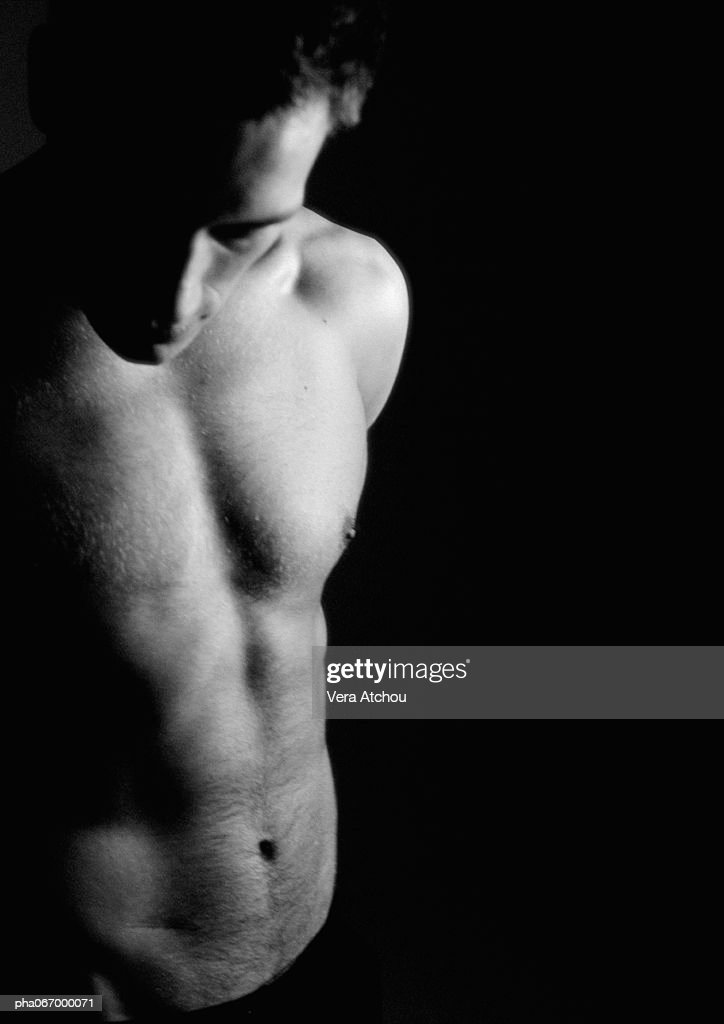 Nude man looking down, partial view, waist up, black and white. : Stockfoto