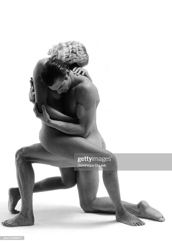 Nude man on one knee embracing nude woman on thigh, B&W : Stockfoto