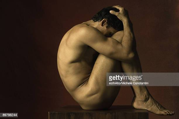Nude man sitting in fetal position, hands on head, side view