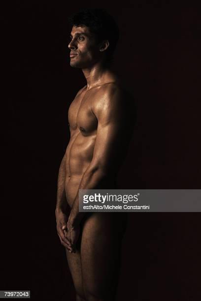 nude man standing in dark, three quarter length - naakte man en profiel stockfoto's en -beelden