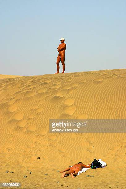 A nude man stands on top of a sand dune and a nude woman tans herself at Maspalomas beach Gran Canaria Canary Islands Spain | Location Maspalomas...