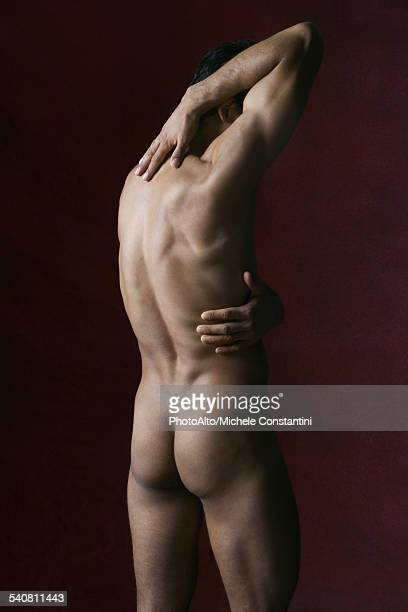 Nude man touching back with both hands
