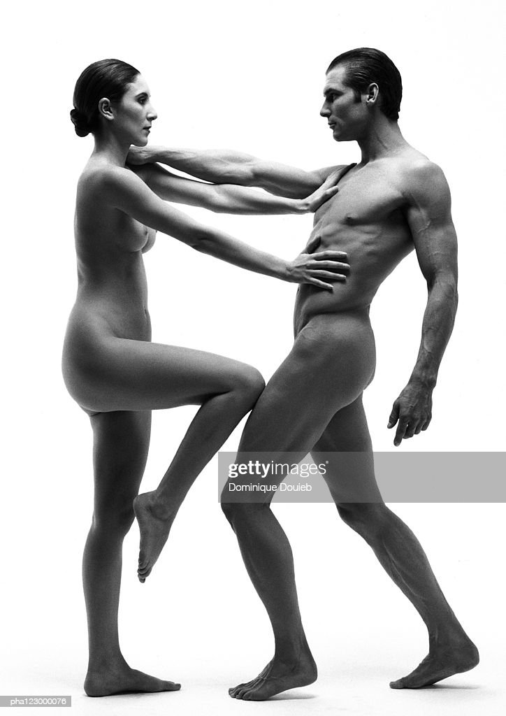 Nude man with arm extended facing nude woman with arms and knee extended, B&W : Stock Photo