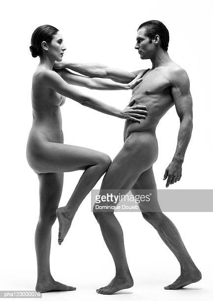 nude man with arm extended facing nude woman with arms and knee extended, b&w - naakte man en profiel stockfoto's en -beelden