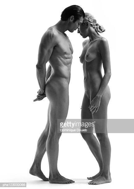 nude man with hands behind back facing nude woman with hands at her side, b&w - naakte man en profiel stockfoto's en -beelden