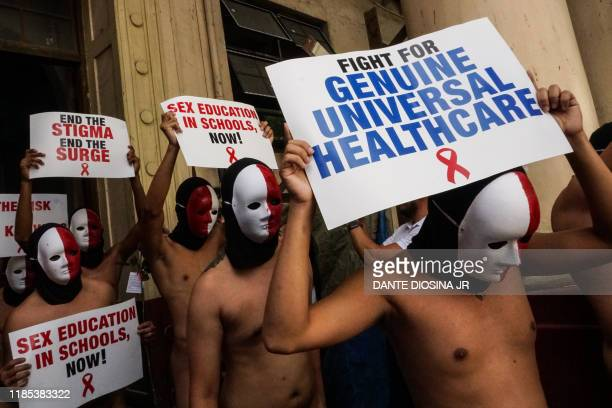 Nude members of a fraternity hold placards as they participate in an Oblation Run at the University of the Philippines campus in Manila on November...