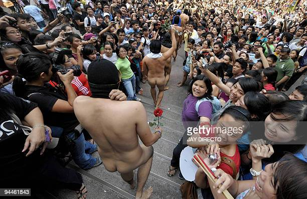 Nude members of the a university fraternity make their way through a crowd of students during the traditional 'Oblation Run' at the University of the...