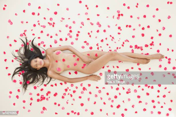 Nude mixed race woman covered with rose petals