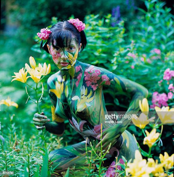 A nude model painted by Elena Mukhanova poses in the artist's garden in the village of Meshersky 20 km from Moscow