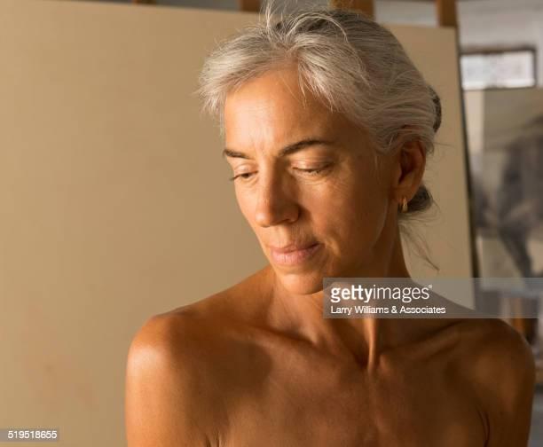 Nude older Caucasian woman modeling for artist in studio