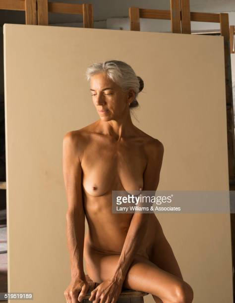 Nude older Caucasian woman modeling for artist in studio