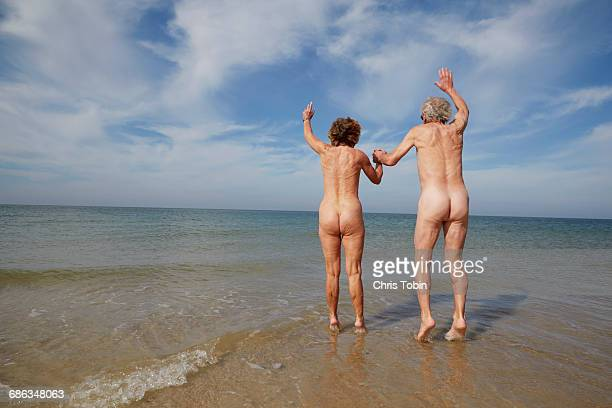 Nude older couple jumping in water