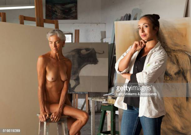 Nude older woman modeling for artist in studio