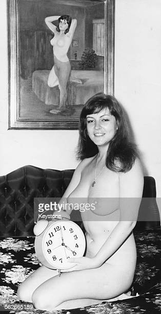 Nude portrait of actress Melitta Tegeler holding a large alarm clock in bed in her apartment in Berlin November 29th 1972