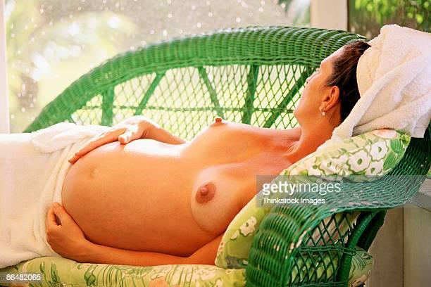 nude pregnant woman lying down - weibliche brust schwanger stock-fotos und bilder