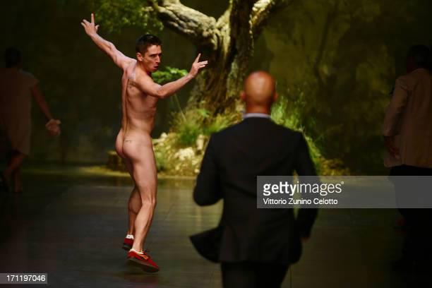 A nude protester is chased from the runway at the Dolce Gabbana show during Milan Menswear Fashion Week Spring Summer 2014 on June 22 2013 in Milan...