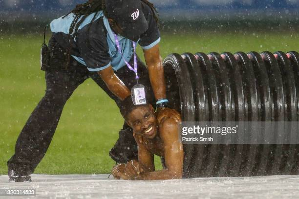 Nude streaker is pulled from the infield tarp roller tube by security during a rain delay between the Cincinnati Reds and against the Washington...