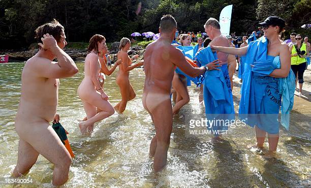 Nude swimmers reach for a sarong after completing the 'Sydney Skinny' in what is dubbed the first mass nude ocean swim in Sydney on February 17 2013...