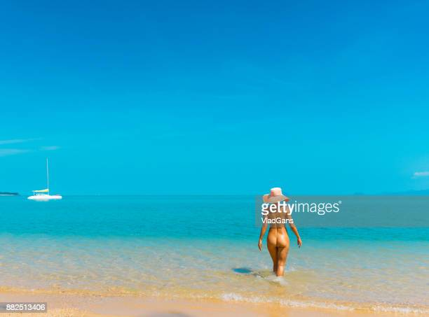 nude woman at tropical beach - naturalist beach stock photos and pictures