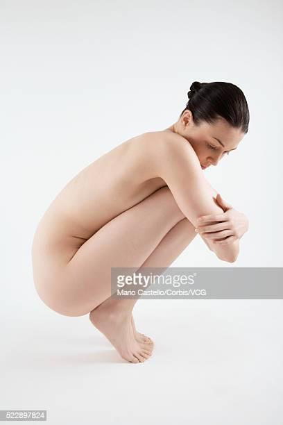 Nude woman crouching