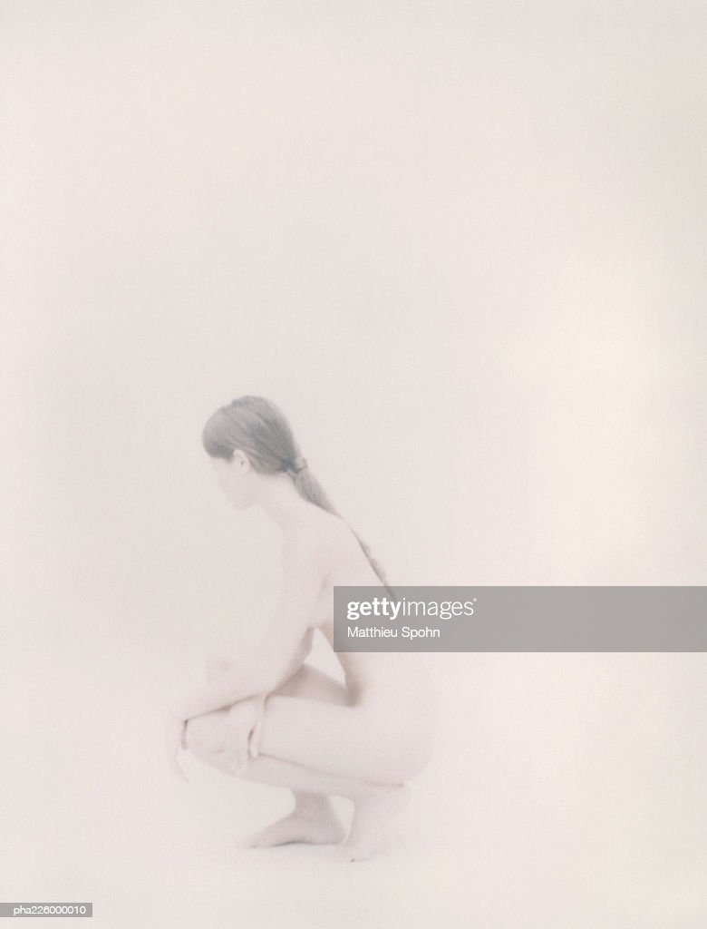 Nude woman crouching, side view. : Stock Photo