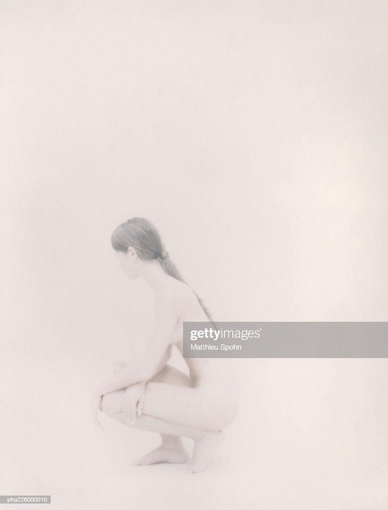 Nude woman crouching, side view. : Stockfoto