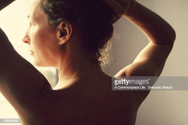 Nude woman gazing out of a window