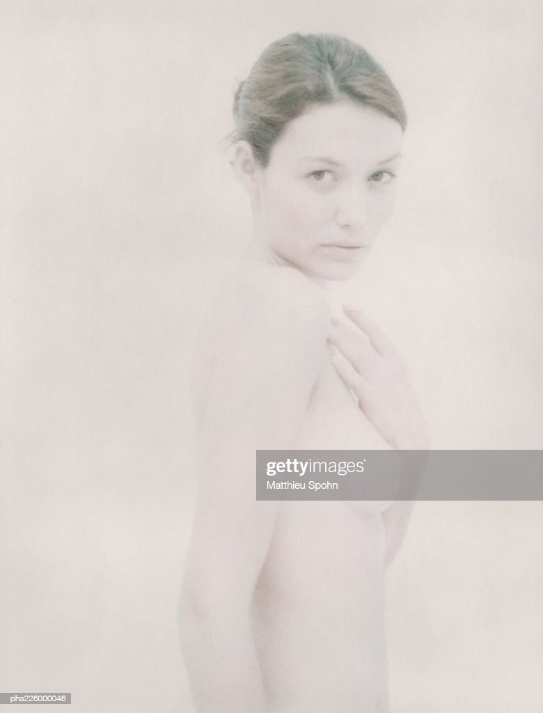 Nude woman, hand on chest,  looking into camera, side view. : Stockfoto