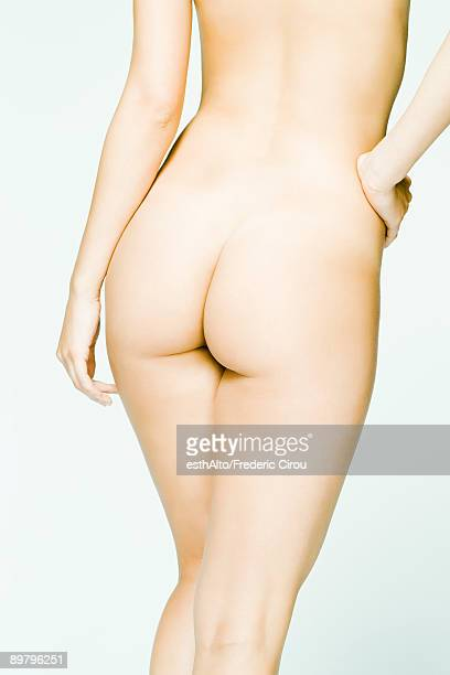 Nude woman, hand on hip, rear view